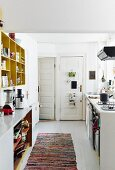 White-painted board floor, colourful rag rug and opposing kitchen counters in bright period apartment