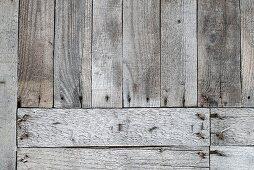 Verwitterte Holzbretter quer und längs genagelt