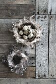 Two wreaths of feathers and quail eggs on weathered wood