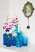 Collection of various blue vases holding orchids and rose