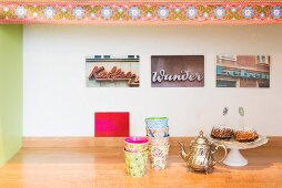 Colourful beakers and vintage jug in front of photos of vintage adverts