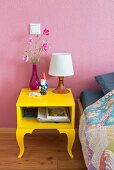 Garden gnome on bright yellow bedside table against pink wall