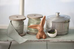 Easter bunny in front of reels of ribbon and vintage tin