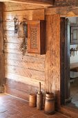 Old butter churns against rustic wooden wall