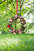 Blumenkranz hängt an einem Ast in der Sommerwiese