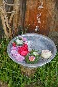 Wasser fliest in eine Schüssel mit schwimmenden Blüten