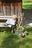 Zinc tub and buckets decorated with flowers outside wooden cabin