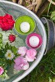 Blumen und Schwimmkerzen in einer Zinkwanne mit Wasser