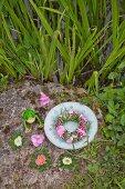 Blumenkranz aus Bartnelken, Hortensien und Gras im Teller