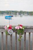 Zwei Metallkörbe mit Blumen und Gras am Geländer zum See