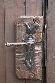 Traditional door handle wit cockerel motif on rustic brown wooden door