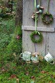 Mit Kränzen und Holzpilzen dekorierter Fensterladen im Wald