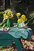 Gelbe Tagetes in Glasflaschen auf einem Metalltablett im Wald