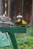 Waage mit Champignons und ein Holpilz auf Moos-Blumen-Gesteck