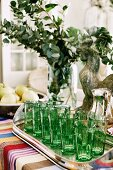Green glasses on silver tray on colourful tablecloth