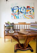 Art-Deco table in front of bench with turned spindles below modern artwork on wall