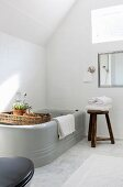 Grey bathtub with rustic accessories under sloping ceiling