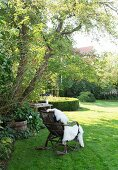 Rattan rocking chair with fur blanket under tree in garden