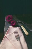 Still-life arrangement of cutlery, pink napkin and roses