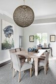 Ceramic pots on chunky dining table and upholstered chairs in elegant interior