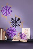 Hand-made paper spiders' webs on purple wall
