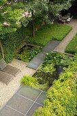 Geometrisch angelegter Garten mit Teich, Gittersteg, Bodendeckern und Outdoormöbeln