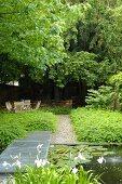 Gitterrost-Steg am Gartenteich und Kiesweg zu schattigem Sitzplatz
