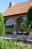Liegestühle vorm Backsteinhaus mit großen Bogenfenstern