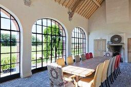 Langer Tisch mit verschiedenfarbigen Stühlen vor Bogenfenstern