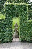 Sculpture framed by opening in clipped hedge