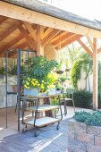 Retro serving trolley and plants in zinc planters in summer house with three open sides