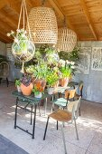 Flowering potted plants on garden table and retro chairs in summer house with three open sides