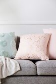 Pastellfarbene Kissen mit Punkten und Tupfen auf grauem Sofa