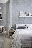 Bedroom in shades of gray with a wiped wall