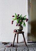 Tulpenstrauß in einer Kaffeekanne aus Zinn auf einem Hocker