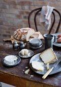Rustikal gedeckter Tisch mit Zinngeschirr, Käse und Brot vor Backsteinwand
