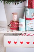 Reels of ribbon and twine and wrapped Christmas gifts on wooden stool with drawer
