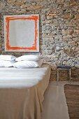 Rustikale Natursteinwand mit modernem Bild in reduziertem Schlafzimmer