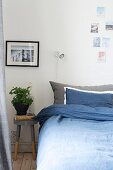 Blue bed linen, stool used as bedside tale and photos decorating wall in bedroom