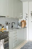 Pale fitted kitchen with wall units, marble worksurface and marble splashback
