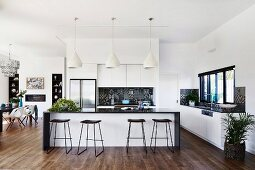 Kitchen with kitchen counter and bar stools in an open, elegant living area