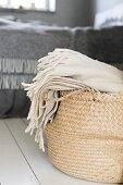 Cream woollen blanket in rattan shopping basket
