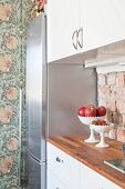 White kitchen counter with unrendered brick splashback next to floral wallpaper