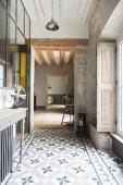 Vintage Flur mit Zementfliesenboden, teilweise Sichtmauerwerk, Fensterladen und Konsolentisch mit Ventilator