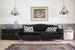 Schwarzes Sofa mit Samtbezug und Kissen, daneben Koffer als Beistelltisch und Kronleuchter