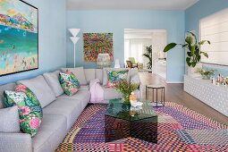 Living room with pastel blue walls, gray corner couch and glass coffee table on colorfully patterned carpet