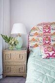 Bedside table with table lamp next to bed with patterned headboard