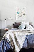 Wolldecke über gemütlichem Bett mit vielen verschiedenen Kissen