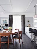 Round cherry wood dining table and chairs in elegant, open kitchen in shades of gray