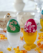 2 colored easter eggs with leaf impression, chicken